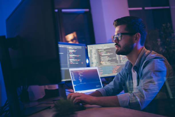 Profile side view portrait of his he nice attractive skilled focused serious guy writing script ai tech support devops creating digital solution front-end in dark room workplace station indoors stock photo