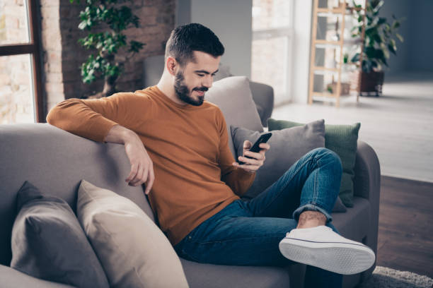 Profile side view portrait of his he nice-looking attractive focused cheerful bearded guy sitting on divan visiting dating service acquaintance at industrial loft brick interior style living-room stock photo
