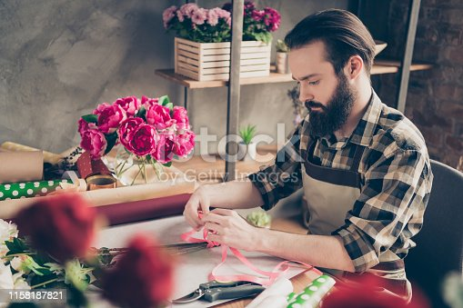istock Profile side view portrait of nice attractive focused guy wearing checked shirt creating new composition celebratory event birthday present gift surprise peony at industrial loft style salon indoors 1158187821