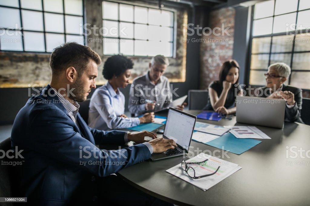 Profilansicht eines Geschäftsmannes mit Laptop auf einem Treffen im Büro. – Foto
