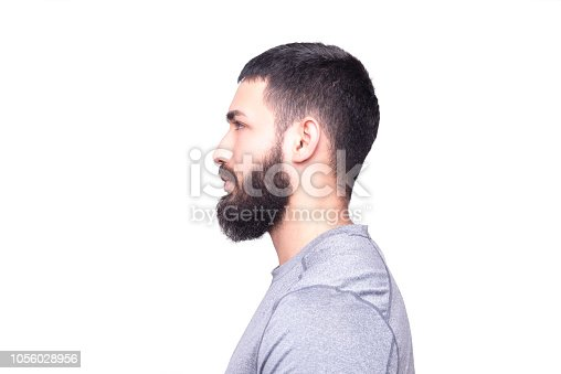 istock Profile view of a handsome young man looking away on a white background 1056028956