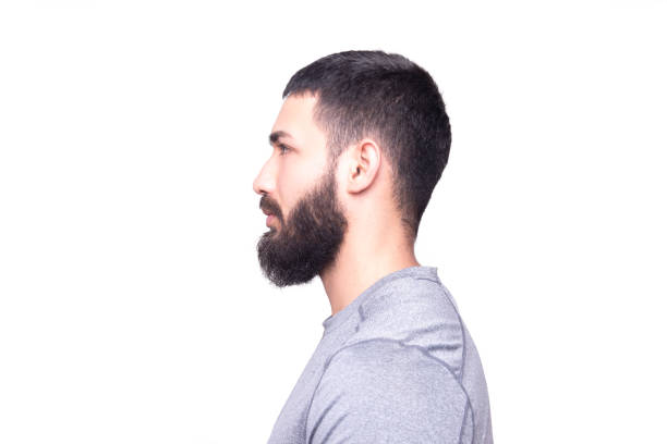 Profile view of a handsome young man looking away on a white background stock photo