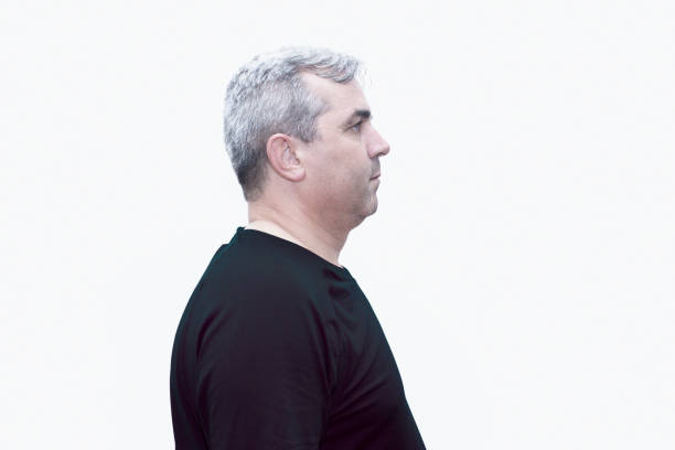 Profile view of a mature man looking away with a blank facial expression over white background