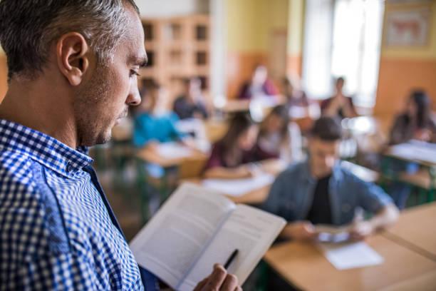 profile view of a professor using a book on a lesson in the classroom. - professore di scuola superiore foto e immagini stock