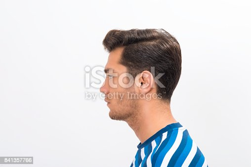 istock Profile view of a young mana standing in front of a white background and looking away with blank facial expression 841357766