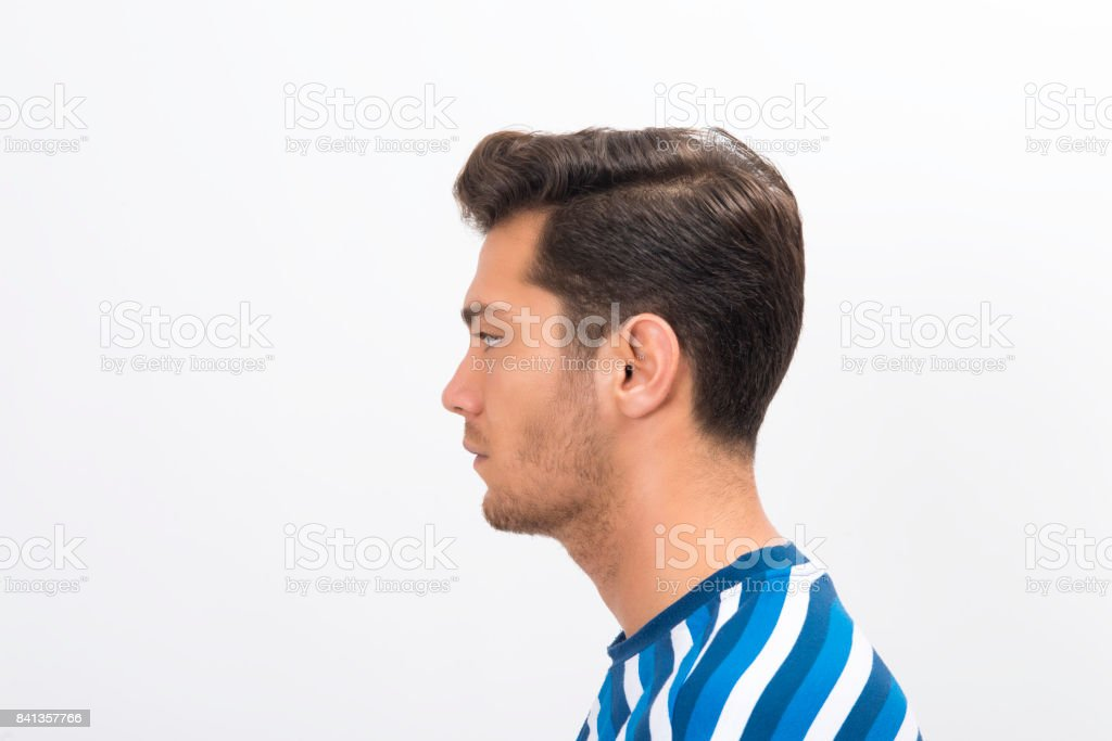 Profile view of a young mana standing in front of a white background and looking away with blank facial expression stock photo
