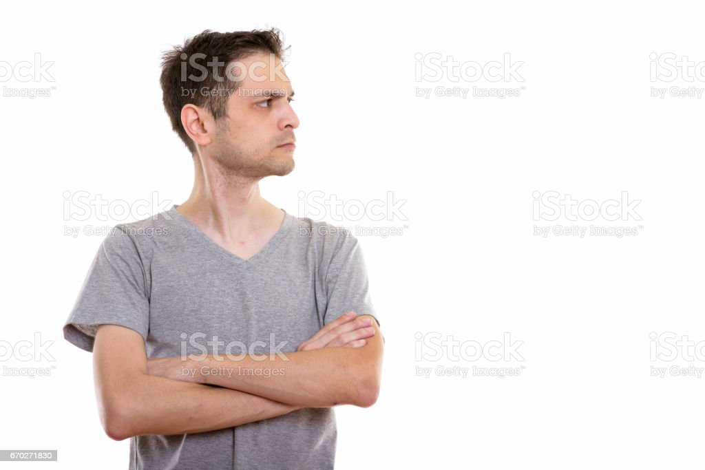 Profile view of angry young man with arms crossed stock photo