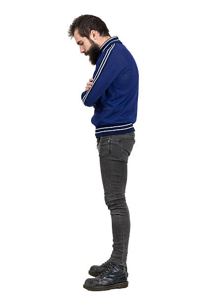 Profile view of bearded hipster in tracksuit jacket looking down Profile view of bearded hipster in blue tracksuit jacket looking down with crossed arms. Full body length portrait isolated over white studio background. men in tight jeans stock pictures, royalty-free photos & images