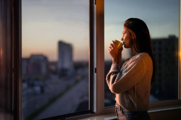 vista de perfil de una hermosa mujer bebiendo café junto a la ventana. - café bebida fotografías e imágenes de stock