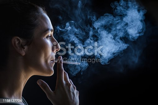 Young woman smoking a cigarette in the dark. Copy space.