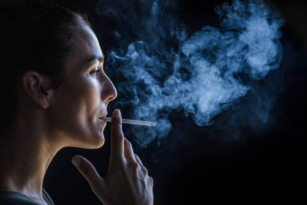 Profile view of beautiful woman smoking in the dark. stock photo