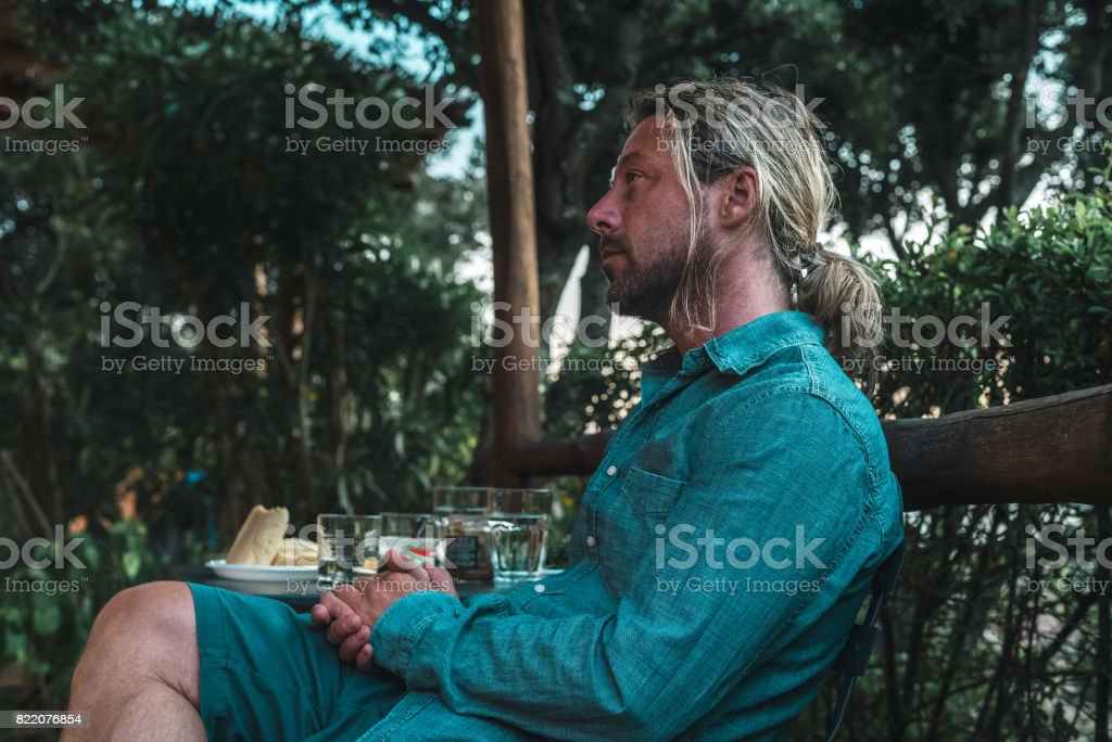 Profile view of casual man with long blond hair sitting outdoor during summer vacation. stock photo