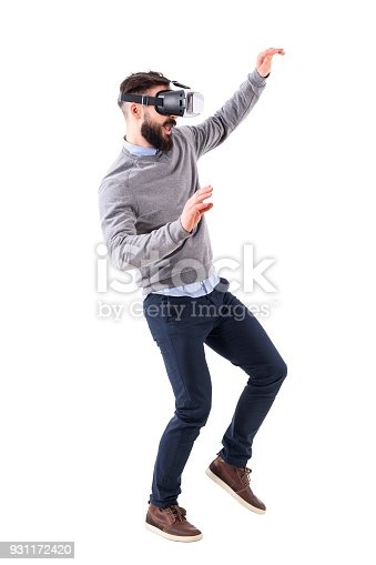 istock Profile view of excited amazed business man wearing virtual reality glasses and waving hands 931172420
