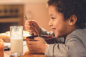 Happy African American boy enjoying in his breakfast at dining table.