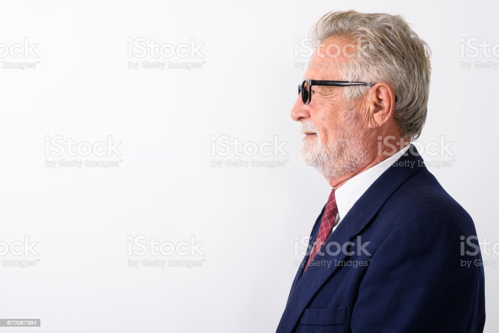 Profile view of happy senior bearded businessman smiling while wearing eyeglasses against white background stock photo