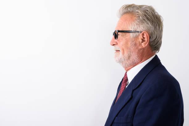 Voir le profil de heureux homme barbu senior souriant tout en portant des lunettes sur fond blanc - Photo