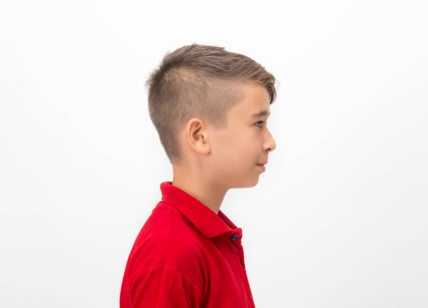 Profile view of little boy standing over white background looking away with blank facial expression stock photo