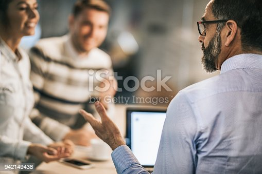 Mature financial advisor communicating with a couple on a meeting in the office.