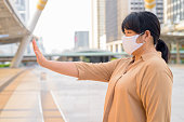 istock Profile view of overweight Asian woman with mask showing stop gesture in the city 1223320726