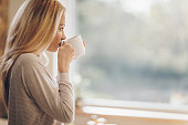 Young beautiful woman enjoying in morning coffee and looking away. Copy space.