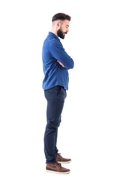 profile view of sad man with bent down head and crossed arms looking down. - guardare verso il basso foto e immagini stock