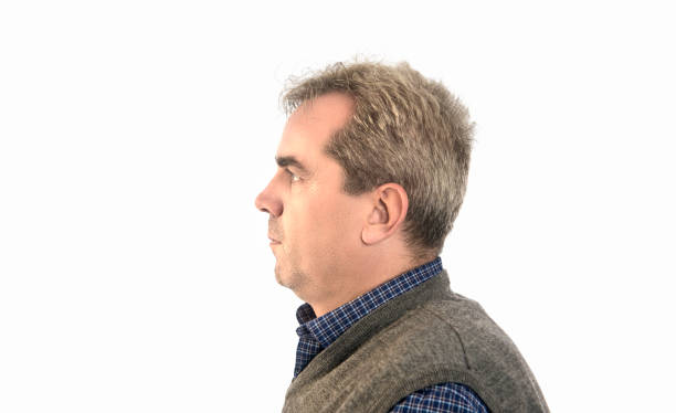 Profile view of serious mature man looking away over white background