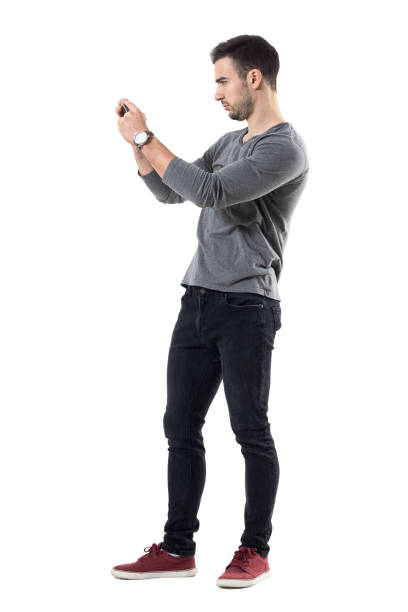 Profile view of serious young casual man holding cellphone taking photo stock photo