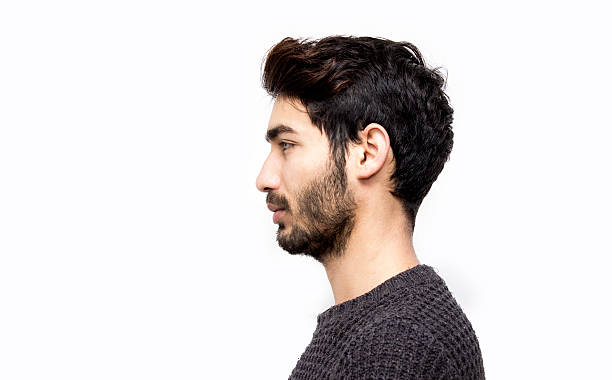 Profile view of serious young man over white background Profile view of serious young man over white background. Mug shot of young man isolated on white. Studio shot. Horizontal composition. Young man has got short black hair and beard. side view stock pictures, royalty-free photos & images