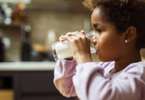 小黑人女孩在家喝牛奶的概況視圖。 - 牛奶 個照片及圖片檔