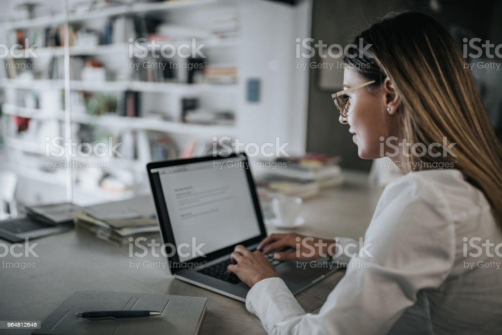 Profile view of smiling businesswoman typing an e-mail on laptop in the office. royalty-free stock photo