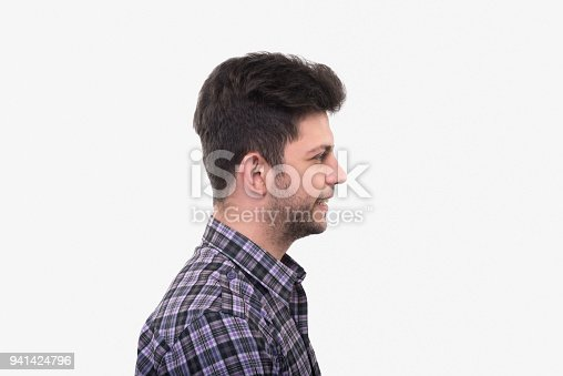 istock Profile view of smiling young man looking away over white background 941424796