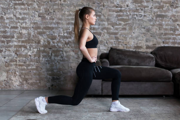 Profile view of sporty girl doing lunges working-out leg muscles and glutes in loft interior stock photo