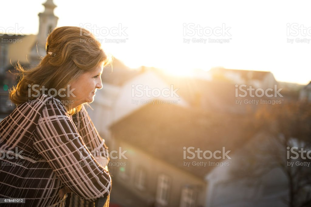 Profile view of thoughtful elderly woman on a terrace at sunset. royalty-free stock photo