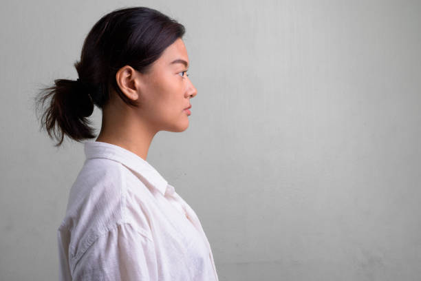 Profile view of young beautiful Asian woman with hair tied Studio shot of young beautiful Asian woman with hair tied against white background profile view stock pictures, royalty-free photos & images