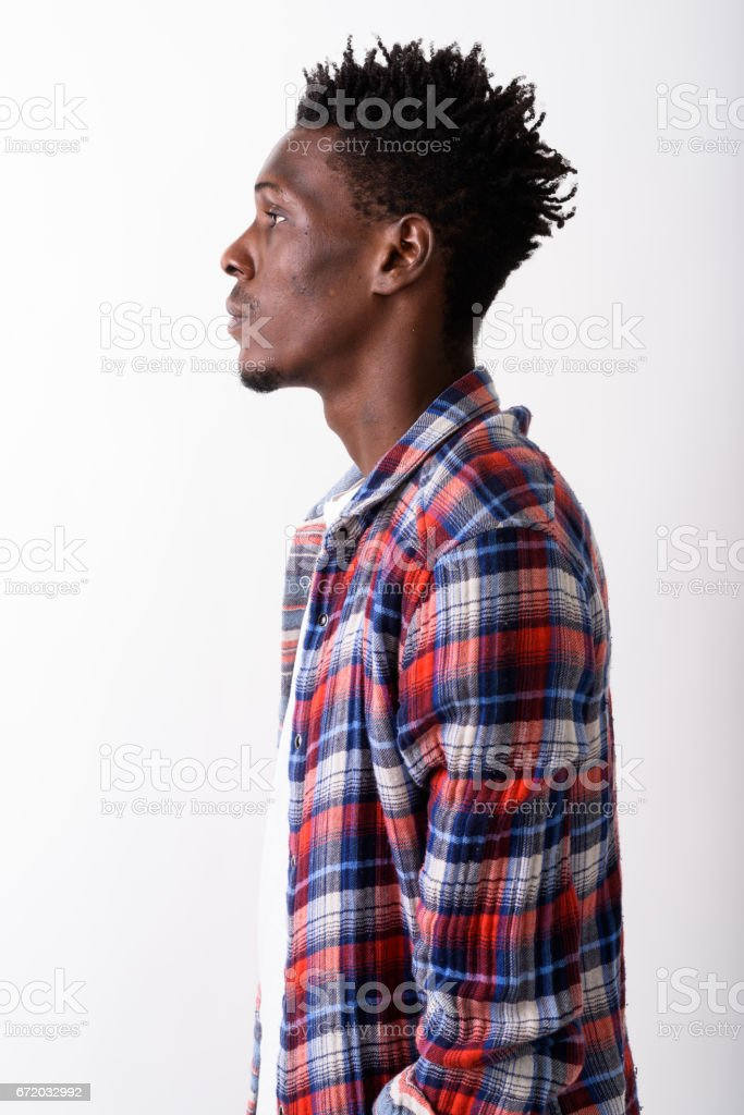 Profile view of young black African man against white background stock photo