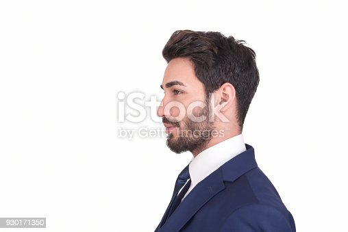 Profile view of young businessman in suit looking away over white background. There is smiling facial expression on his face. Side view, studio shot. Horizontal composition. Studio shot. Image taken with Nikon D800 and developed from Raw format.