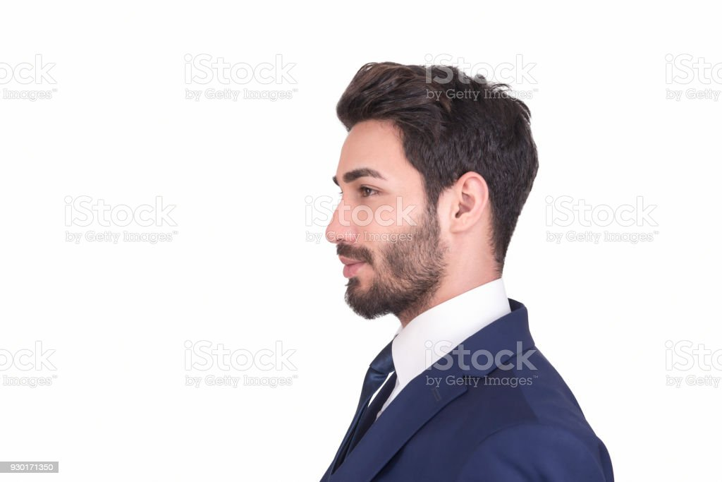Profile view of young businessman in navy blue suit looking away over white background stock photo