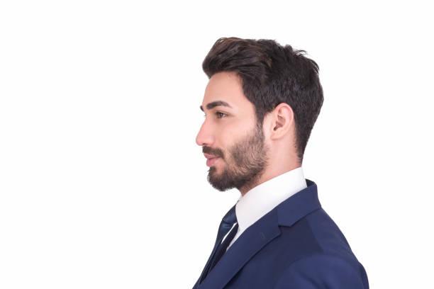 Voir le profil de jeune homme d'affaires en costume bleu marine donnant loin sur fond blanc - Photo