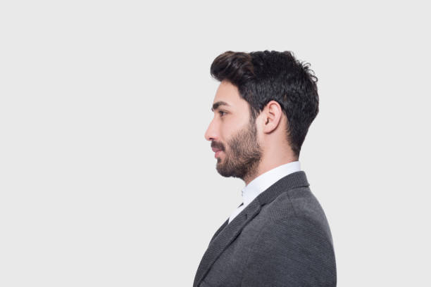 Profile view of young businessman in suit looking away over gray background stock photo