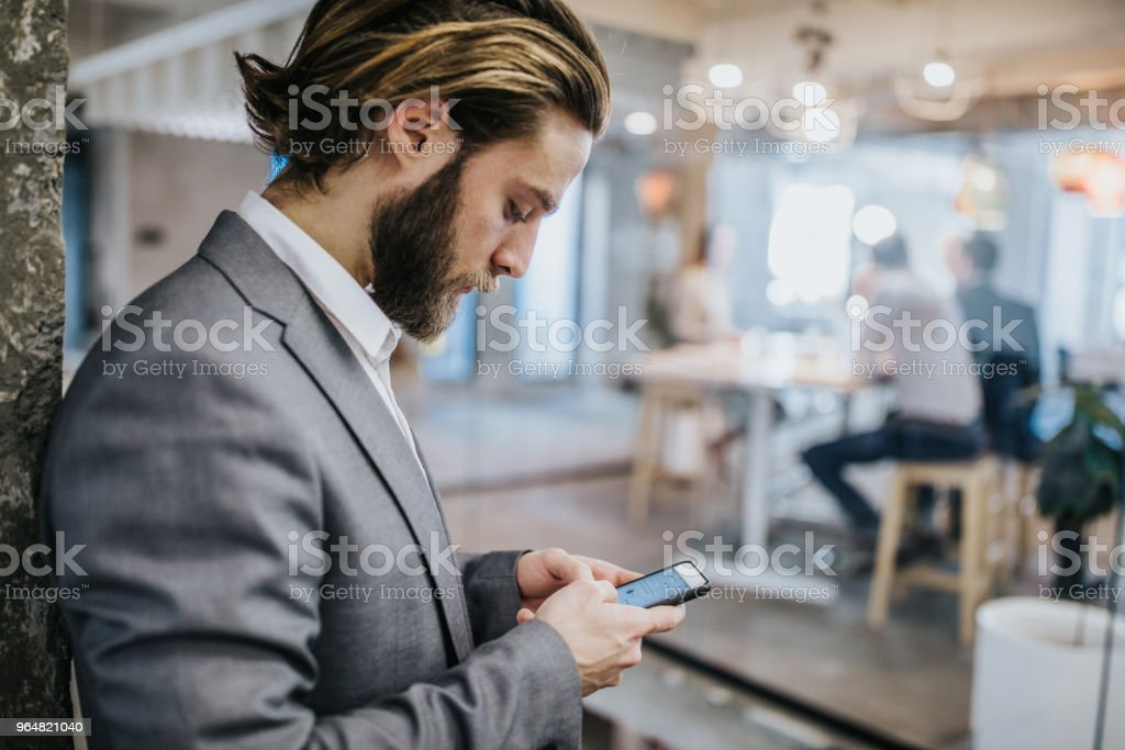Profile view of young businessman text messaging on cell phone. royalty-free stock photo