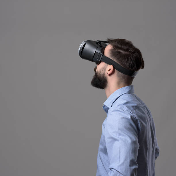 profile view of young businessman wearing smartphone vr headset looking up at copyspace - ritratto 360 gradi foto e immagini stock