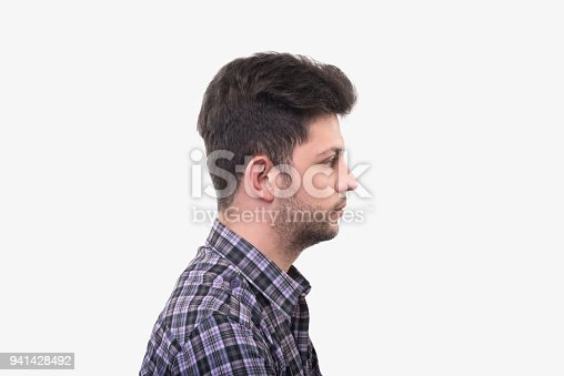 istock Profile view of young man looking away with blank facial expression over white background 941428492