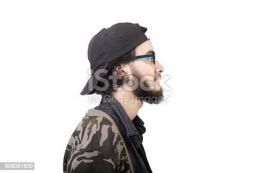 istock Profile view of young man looking away with blank facial expression by standing on a white background 956081800