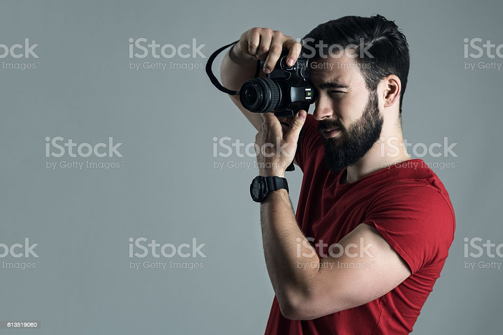 Profile view of young man taking photo with digital camera stock photo