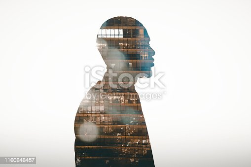 Profile view silhouette of businessman double exposed with city at night