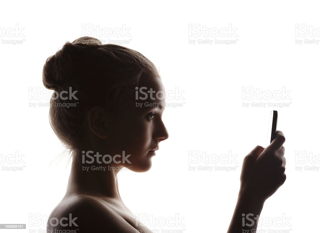 Profiled woman holding a phone on a glowing white background stock photo
