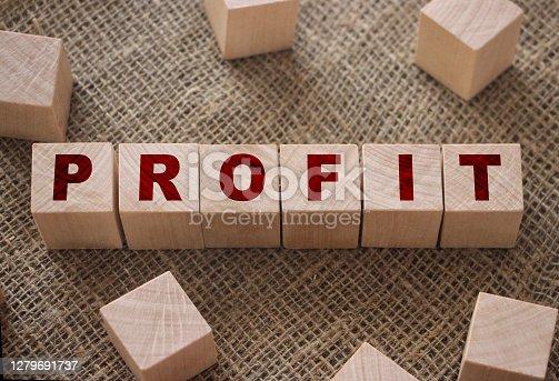Profit text written on wooden block on burlap canvas background. Business profitability concept.
