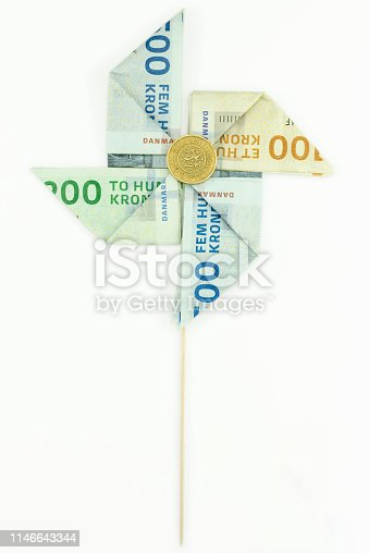Studio shot of a pinwheel made of Danish kroner notes and coin: 500, 200 and 100 kr, and a 10 kr coin.