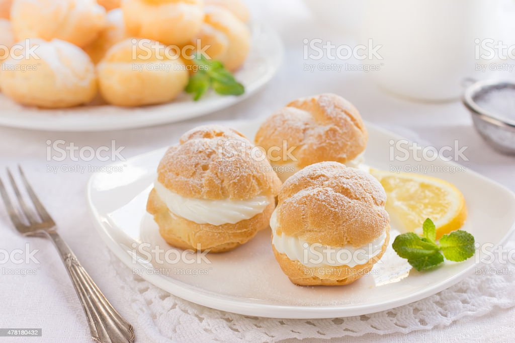 profiteroles with cream and powdered sugar stock photo