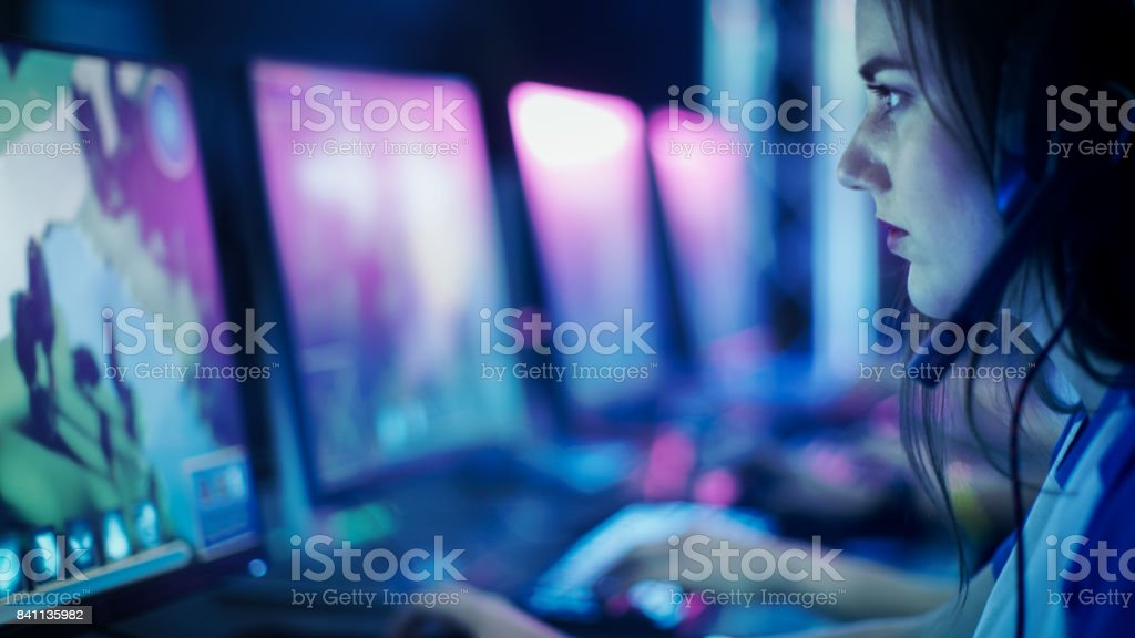 Progamer Girl Playing in MMORPG/ Strategy Video Game and Participating in Online Cyber Games Tournament or Playing in Internet Cafe. stock photo